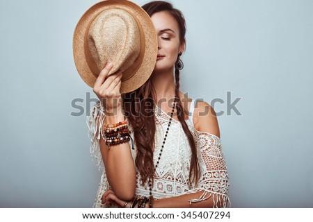 Portrait of beautiful young hippie woman wearing hat in studio #345407294