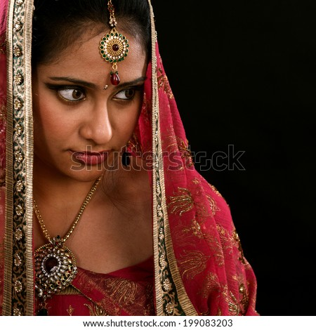 Portrait of beautiful young Indian girl looking to copy space at side isolated on black background