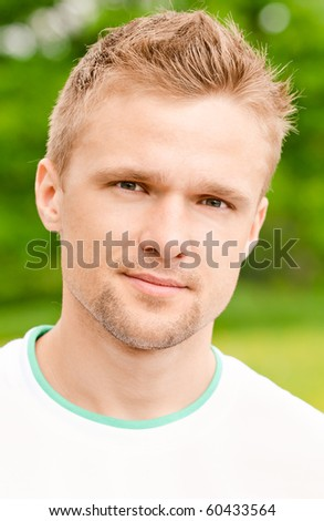 Portrait of beautiful young man against summer garden.