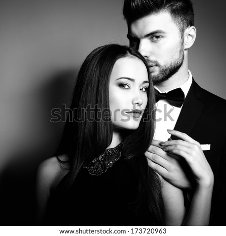 Portrait of beautiful young man and woman dressed in classic clothes, studio shot over grey background. Sexy passion couple in love.