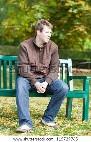 Portrait of beautiful young man in the autumn park sitting on bench