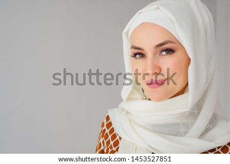 Portrait of beautiful young muslim arabian woman wearing white hijab looking at camera, copy space