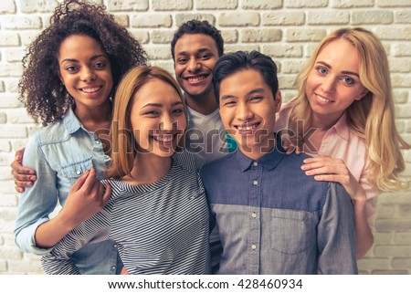 Portrait of beautiful young people of different nationalities looking at camera and smiling, against white brick wall
