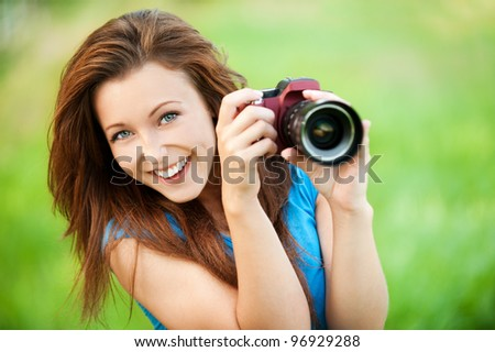 Portrait of beautiful young smiling woman with camera at summer green park