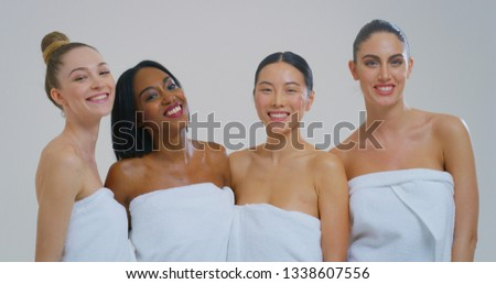 Portrait of beautiful young smiling women of different ethnicities with perfect firm and slim body in white bathing towels isolated on white background.