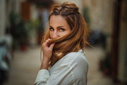 Portrait of beautiful, young, stylish Women Tourist Traveler playing with her Hair in the Streets of Bari, Italy. Street fashion. Holliday, Travel Concept.