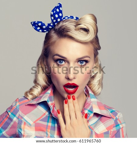 Portrait of beautiful young surprised woman, dressed in pin-up style. Caucasian blond model posing in retro fashion and vintage concept studio shoot, on grey background.