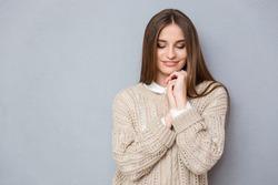 Portrait of beautiful young sweet shy pretty girl in beige sweater looking down
