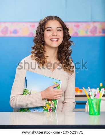 Portrait of beautiful young teacher with book sitting at desk in preschool