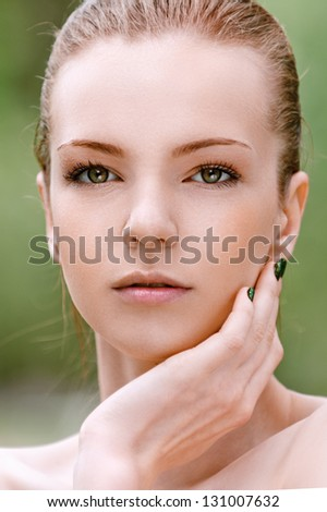 Portrait of beautiful young woman, against background of summer green park.
