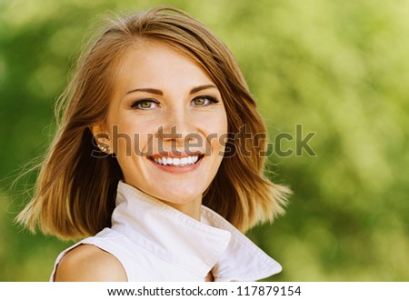 Portrait of beautiful young woman, against green of summer park.