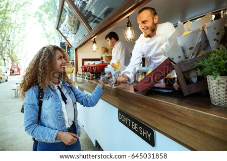 Portrait of beautiful young woman buying barbecue potatoes on a food truck in the park.