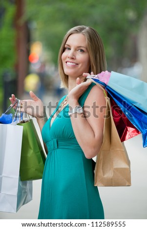Portrait of beautiful young woman carrying shopping bags