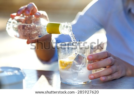 Portrait of beautiful young woman drinking soda in a restaurant terrace.