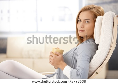 Portrait of beautiful young woman drinking tea in armchair, smiling.?