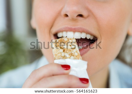 Portrait of beautiful young woman eating muesli snack at home. Сток-фото ©