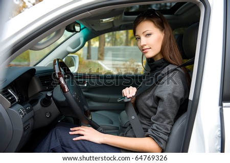 Portrait of beautiful young woman fastens a seat belt in the car - outdoors - stock photo