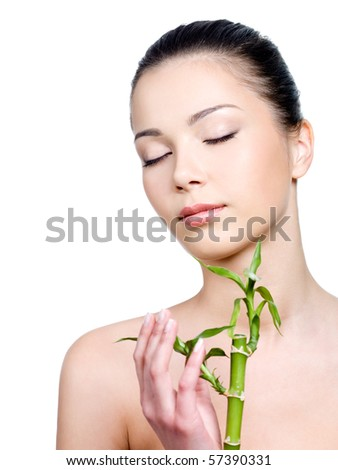 Portrait of beautiful young woman having a clean fresh skin on the face and holding plant - stock photo