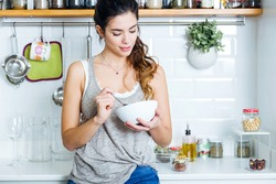 Portrait of beautiful young woman having breakfast in the kitchen.