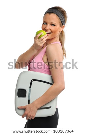 Portrait of beautiful young woman holding scale and apple isolated over white background