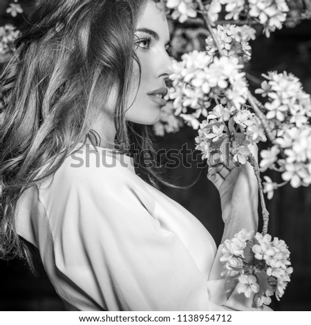 Portrait of beautiful young woman in autumn garden against blooming cherry. Black-white photo. #1138954712
