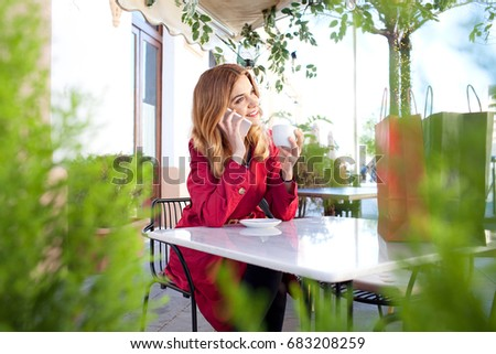 Portrait of beautiful young woman in coffee shop terrace, relaxing using smart phone, phone call conversation outdoors. Fashion female using technology, smiling in city exterior, recreation lifestyle.