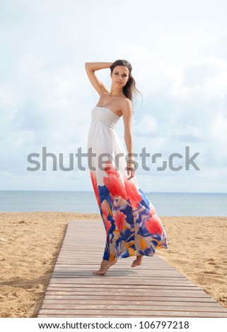 Portrait of beautiful young woman in colorful dress resting at beach in summer
