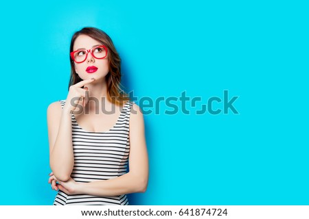 portrait of beautiful young woman in glasses on the wonderful blue studio background