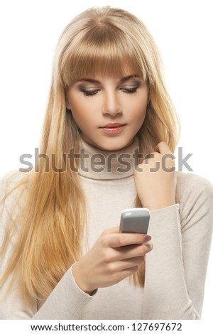Portrait of beautiful young woman in gray sweater with telephone, isolated on white background.