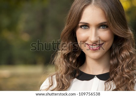 Portrait of beautiful young woman in the park - stock photo