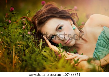 Portrait of beautiful young woman in the sun flare with flowers