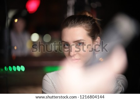 Portrait of beautiful young woman looking at camera over lights in background. the blurred foreground #1216804144