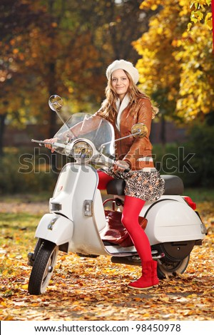 Portrait of beautiful young woman on scooter posing in the park
