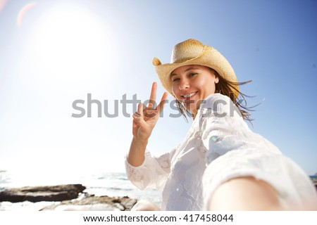 Portrait of beautiful young woman on vacation at the beach taking selfie and gesturing peace sign #417458044