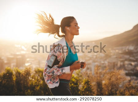 Portrait of beautiful young woman out for a run on a hot sunny day. Caucasian female model jogging outdoors.