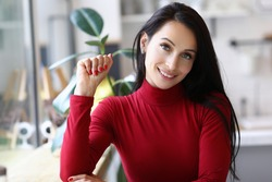 Portrait of beautiful young woman posing on camera sitting in personal office. Stylish pretty female in red blouse and fresh manicure. Smiling businesswoman with makeup. Business and beauty concept