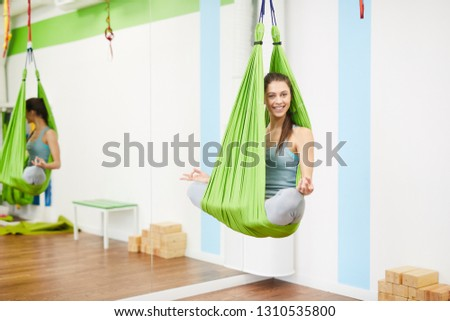 Portrait of beautiful young woman practicing aerial yoga in hammock and looking at camera, copy space, copy space