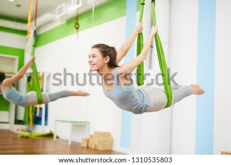 Portrait of beautiful young woman practicing aerial yoga in hammock and smiling, copy space, copy space