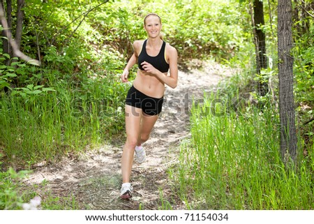 Portrait of beautiful young woman running in the forest
