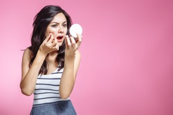 Portrait of beautiful young woman squeezing pimples while looking at the mirror.