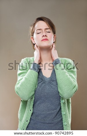 Portrait of beautiful young woman stressed out by neck pains.