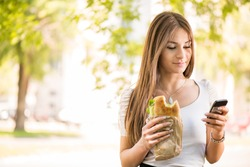 Portrait of beautiful young woman taking a break for breakfast and using a Cell Phone Outdoors.