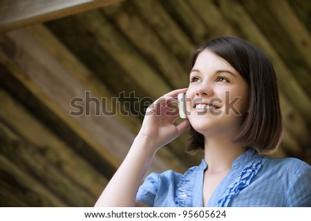 Portrait of beautiful young woman talking at the cell phone - stock photo