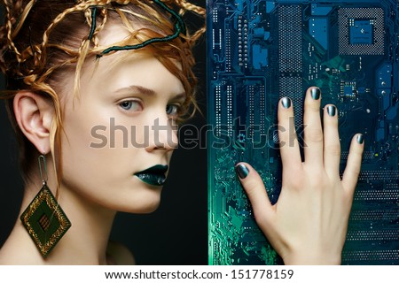 portrait of beautiful young woman touching motherboard with manicured hand