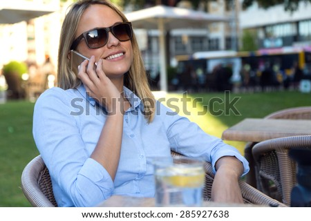Portrait of beautiful young woman using her mobile phone in a restaurant terrace.