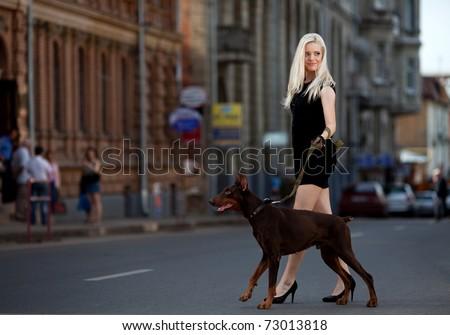 Portrait of beautiful young woman walking a dog
