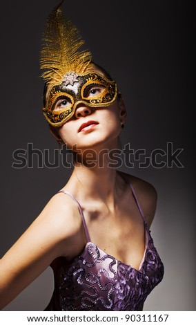 Portrait of beautiful young woman wearing black carnival mask