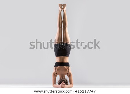Portrait of beautiful young woman wearing black sportswear working out in studio. Fit sporty girl doing advanced yoga, pilates, fitness. Supported headstand, salamba sirsasana. Full length. Rear view