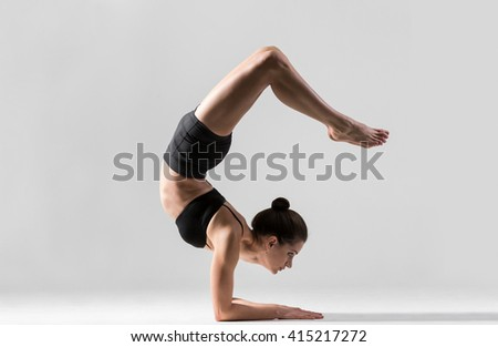 Portrait of beautiful young woman wearing black sportswear working out in studio. Fit yogi girl doing advanced inversion and arm-balance Scorpion Handstand. Vrischikasana. Full length. Side view image