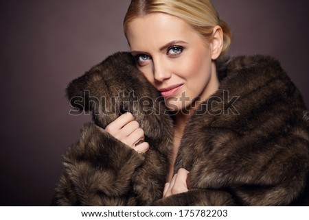 Portrait of beautiful young woman wearing fashionable fur , looking at camera.  #175782203